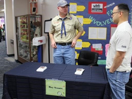People talking at the Boy Scout table display