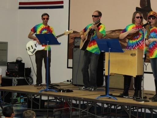 Staff as Artist assembly.  Staff on stage playing music