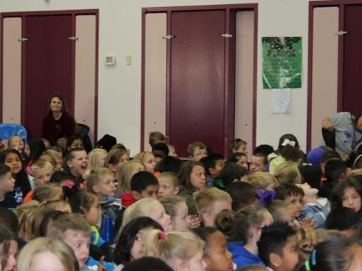 Staff as Artist assembly.  Students watching the show