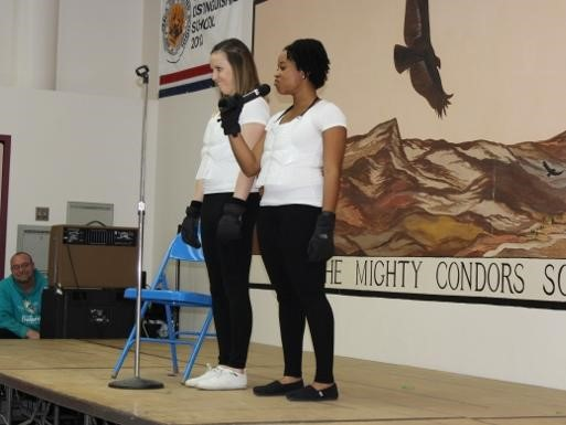 Staff as Artist assembly.  Staff on stage singing