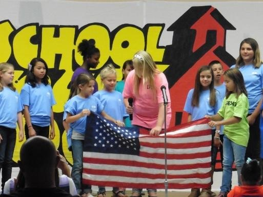 Students on stage for School House Rocks assembly holding american flag