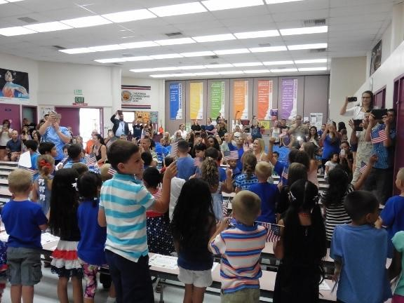 Students hold small american flags at awards assembly