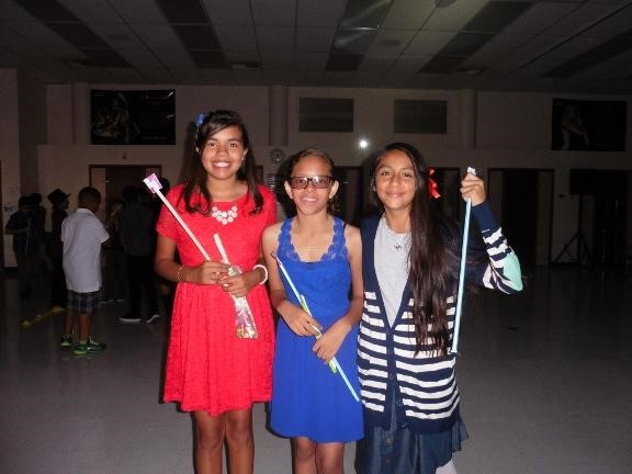 Students at 6th grade dance holding pixy stik candy