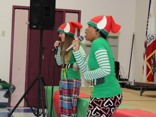 Two staff members singing at the Winter Celebration Assembly
