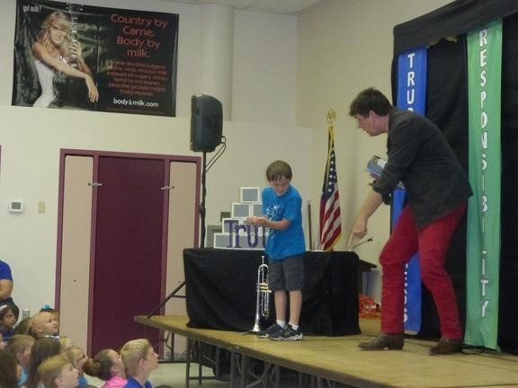 Teacher and students on stage at the Character Counts Assembly