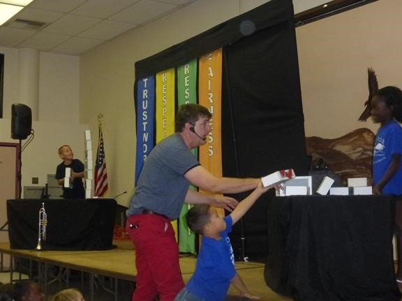 Teacher helping a student get a box from a table