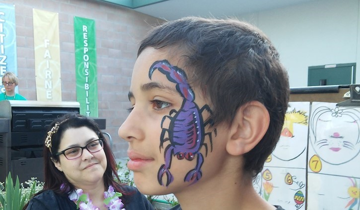 Boy with scorpion face paint