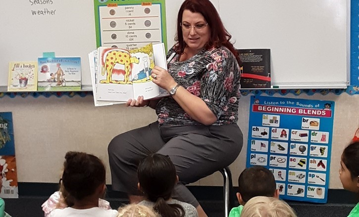 redhead woman reads to children