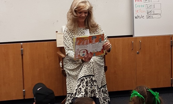 older blonde woman reads to children