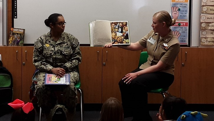 two military women read to children