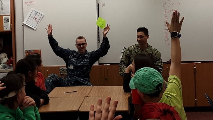 military woman and military man read to children