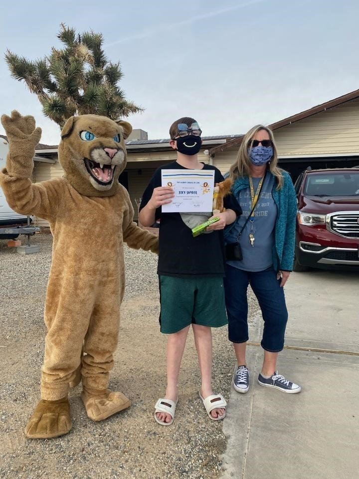 Masked Singer Competition Winner, Joey Snyder, with the Lion Mascot and Mrs. Lafferty, the Masked Singer of the Week