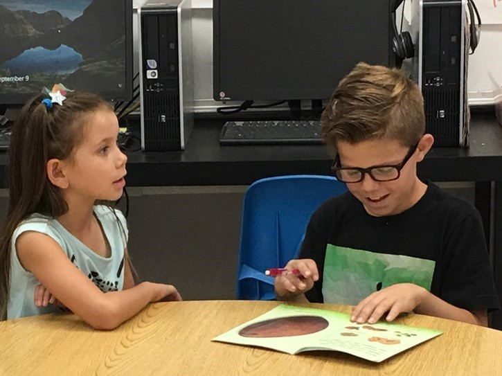 A 4th grader reads to his reading buddy