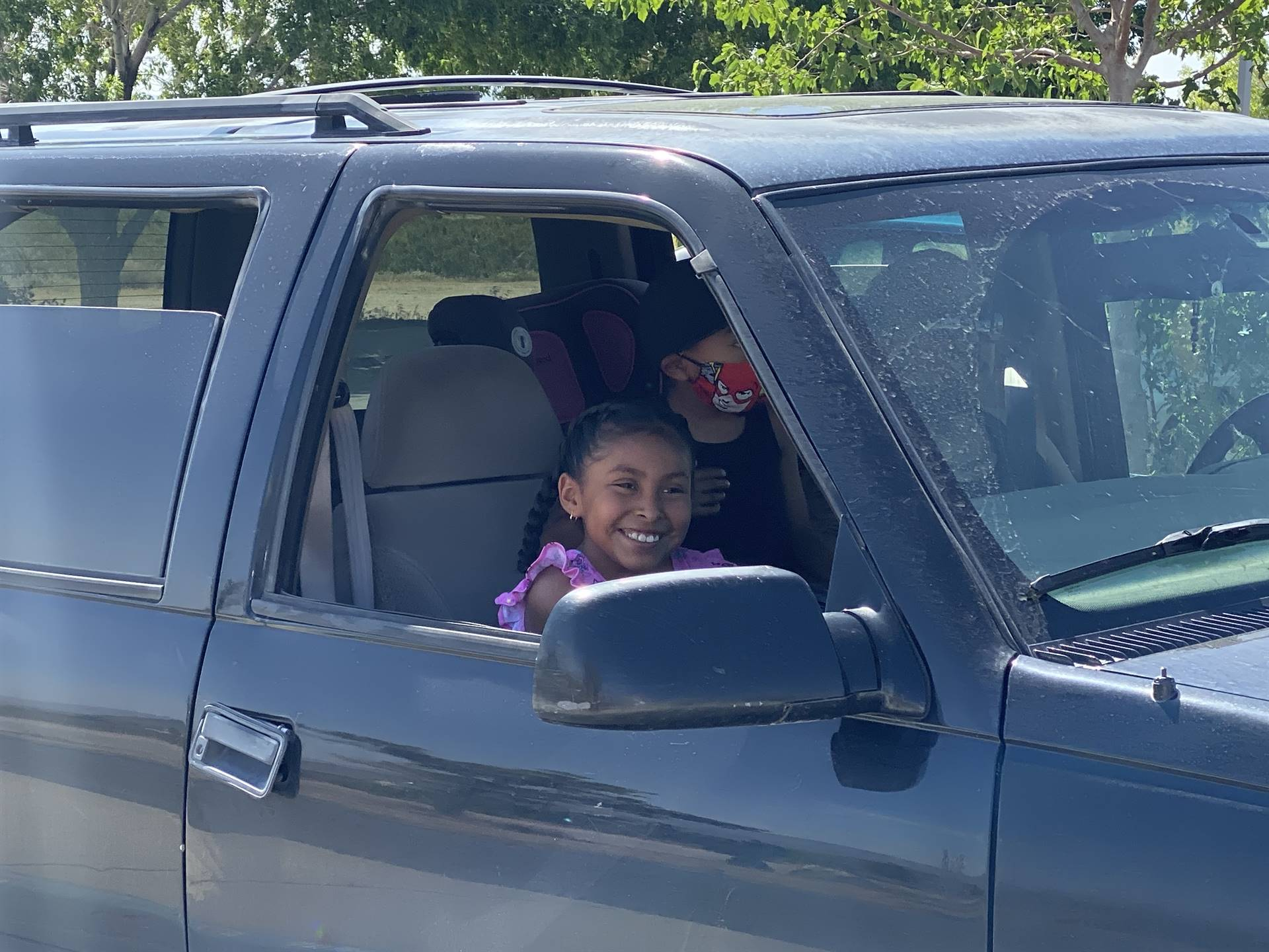 Students wave to teachers safely from their cars