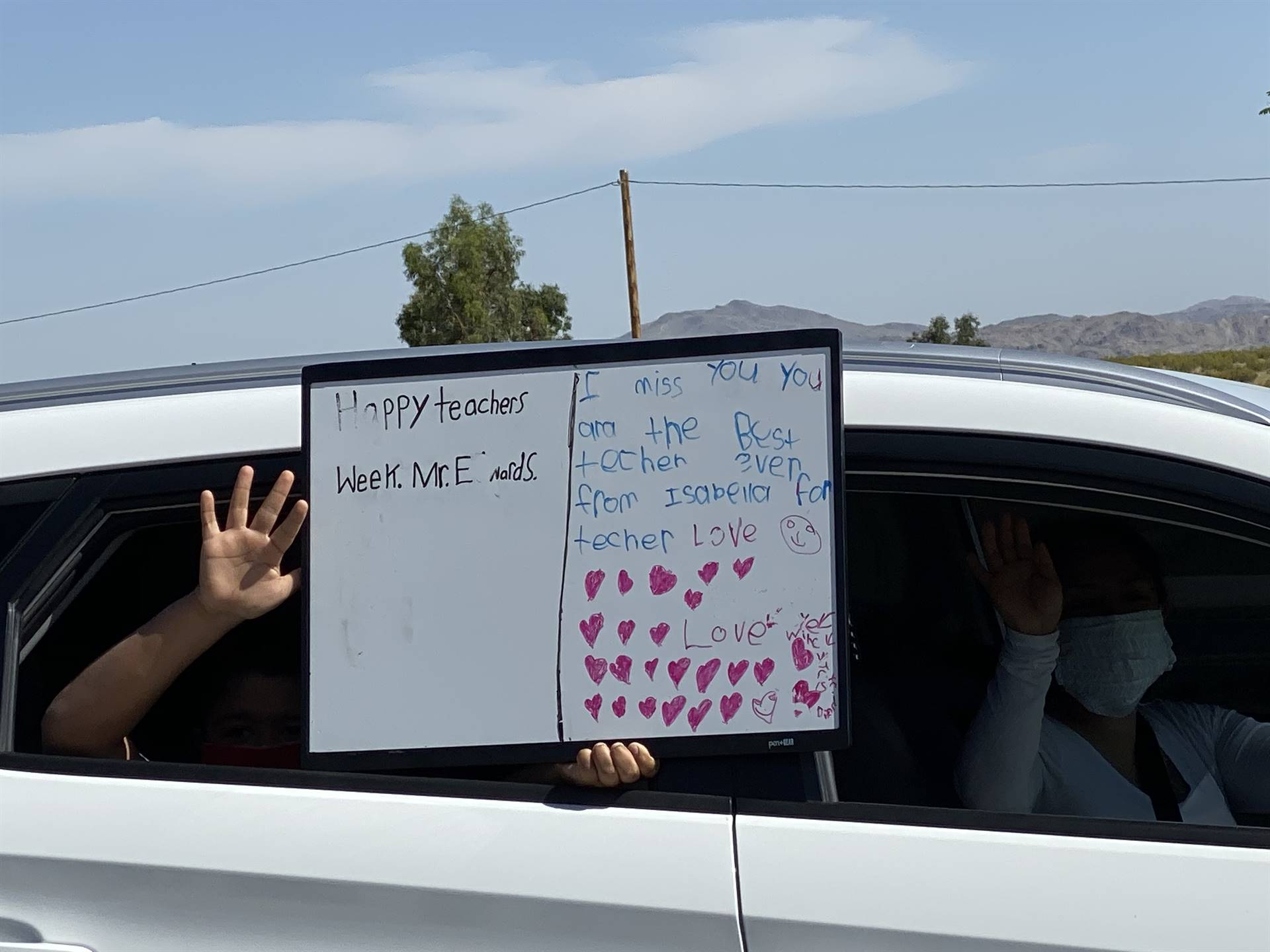 Students wave to teachers with signs of appreciation