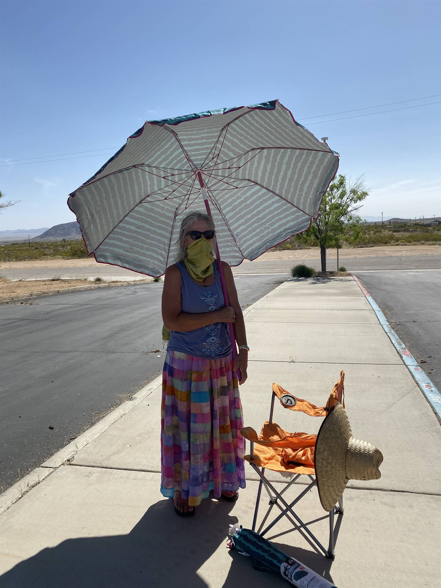 Mrs. Pfarr says hello to students from the shade of her umbrella